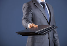 Businessman giving folders to you Royalty Free Stock Image