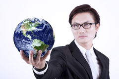Businessman giving globe - isolated. Asian businessman looking smart with glasses holding a globe on white background Royalty Free Stock Image