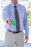 Businessman giving green business card Stock Image