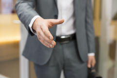 Businessman giving a hand in office Royalty Free Stock Images