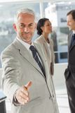 Businessman giving a handshake with colleagues behind Royalty Free Stock Photo