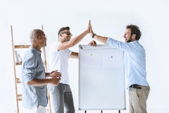 Businessman giving high five to colleague during strategy discussion. In office stock photos