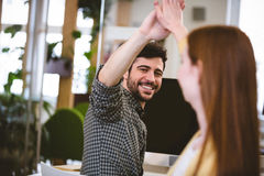 Businessman giving high-five to female coworker Stock Images