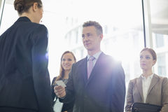 Businessman giving his card to female coworker in office Royalty Free Stock Photography