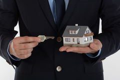 Businessman giving a key and holding small house Stock Image