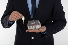 Businessman giving a key and holding small house Royalty Free Stock Photos