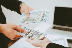 Businessman giving money to business woman. Hand receiving money, US dollar Stock Photos