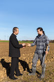 Businessman is giving money to a farmer Royalty Free Stock Photos
