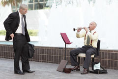 Businessman giving money to the instrument player Royalty Free Stock Images