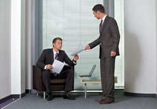Businessman giving paper to colleague in office Stock Image