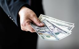 Businessman giving or paying money, US dollar bills - bribery, loan and financial concepts, Stock Images
