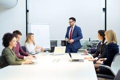Businessman giving a presentation on flip chart. Teamwork concept Stock Photos