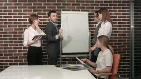 Businessman giving a presentation on flipchart. Teamwork concept stock images