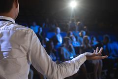 Businessman giving presentation in front of audience in auditorium. Rear view of Caucasian businessman giving presentation in front of audience in auditorium stock photography
