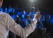 Businessman giving presentation in front of audience in auditorium royalty free stock photo