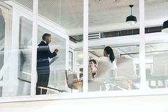 Businessman giving a presentation in modern office with glass walls stock photography