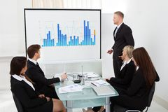 Businessman giving presentation in office. Businessman giving presentation on projector screen to colleagues in office stock photo