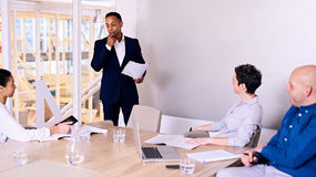 Businessman giving presentation to 3 board member in conference room stock images