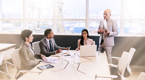 Businessman giving a presentation to colleagues in conference room stock image