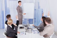 Businessman giving presentation to colleagues at office. Business people with hands raised answering businessman in meeting at office stock photo