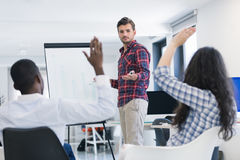 Businessman giving a presentation to his colleagues at work. Standing in front of a flipchart with notes and diagrams royalty free stock photo