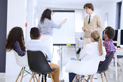 Businessman giving a presentation to his colleagues at work standing in front of a flipchart. With notes and diagrams royalty free stock photo