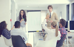 Businessman giving a presentation to his colleagues at work standing in front of a flipchart Royalty Free Stock Photos