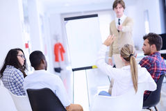 Businessman giving a presentation to his colleagues at work standing in front of a flipchart Royalty Free Stock Image