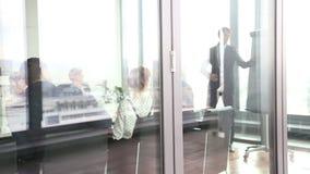 Businessman giving presentation using flipchart behind glass wall stock video