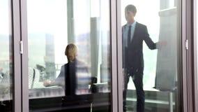 Businessman giving presentation using flipchart behind glass wall stock video footage
