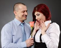 Businessman giving a rose to his partner Stock Photo