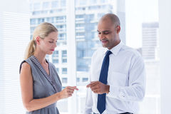 Businessman giving small paper sheet to his colleague Stock Photo