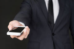 Businessman giving Smart phone to you Stock Images
