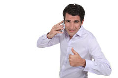 Businessman giving the thumb up. A businessman over the phone giving the thumb up Stock Photos