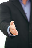 Businessman giving a thumbs up. Cropped view image of the hand of a businessman giving a thumbs up gesture of approval , acceptance and success Stock Image
