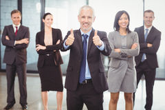 Businessman giving a thumbs up and businesspeople standing with arms crossed Stock Photos
