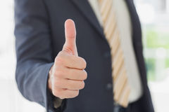 Businessman giving thumbs up Stock Photo