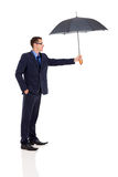 Businessman giving umbrella Stock Images