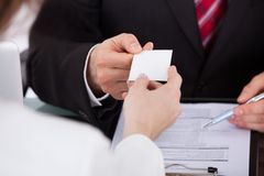 Businessman giving visiting card to colleague at desk. Close-up of businessman giving visiting card to female colleague at desk in office Royalty Free Stock Images