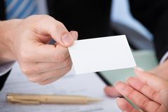 Businessman giving visiting card to woman. Cropped image of businessman giving visiting card to woman in office Royalty Free Stock Photo