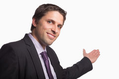 Businessman giving a welcome gesture against white background Royalty Free Stock Image