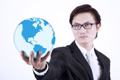 Businessman giving world globe on white. Asian businessman looking smart with glasses holding a globe on white background Stock Images