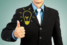 Businessman giving you thumbs up light bulb idea Stock Image