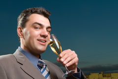 Businessman with a glass of champagne close up Stock Images