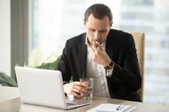 Businessman with glass of water takes round pill Stock Image