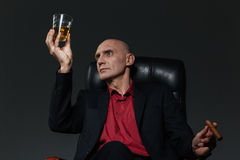 Businessman with glass of whiskey and cigar sitting in chair Stock Images