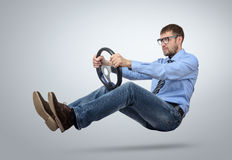 Businessman in glasses car driver with a steering wheel. On background Stock Photos