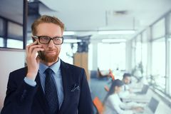 Man talking on the phone. Businessman in glasses communicates by phone. A men makes a working phone call. Boss smiles during conversation royalty free stock photography