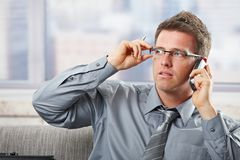 Businessman with glasses on phonecall. Businessman reaching up to glasses concentrating to mobile phonecall holding pen Royalty Free Stock Image