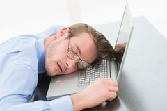 Businessman with glasses sleeping on laptop Royalty Free Stock Photography